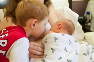 Sibling kissing new baby
